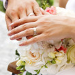 Hands and rings on wedding bouquet — Stock Photo #8827340