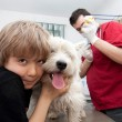Little boy holding his Westie at the veterinarian — Stock Photo #8827447