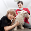 Little boy holding his Westie at the veterinarian — Stock Photo #8827492