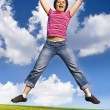 Stock Photo: Jumping woman on a sunny day against a blue sky
