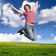 Jumping woman on a sunny day against a blue sky — Stock Photo