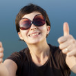 Young brunette girl with big funny sunglasses making thumbs up gesture — Stock Photo
