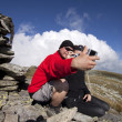 Hiker couple taking pictures up in the mountains — Stock Photo
