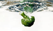 Broccoli falling into water — Stock Photo