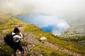Hiker taking photos at Capra lake in Fagaras mountains, Romania — Stock Photo