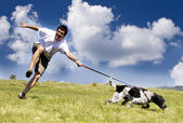 Man playing with his dog on sunny summer day — Stock Photo