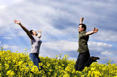 Young couple having fun in summer rapeseed field — Stock Photo