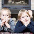 Siblings on floor looking at something — Stock Photo