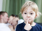 Blonde little girl making silence sign while mom and dad kissing in the background — Stock Photo