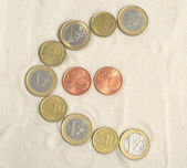 Symbol of euro with euro coins — Stock Photo
