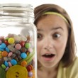 Stock Photo: Girl looking at sweet jar