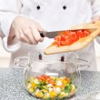 Chef adds chopped tomatoes in a glass bowl - Stok fotoğraf