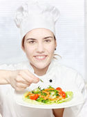 Young chef decorating delicious salad — Stock Photo
