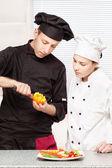 старший повар учит молодой шеф-повар украсить фруктами — Стоковое фото