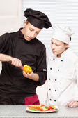 Senior chef teaches young chef to decorate fruit — ストック写真