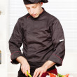 Chef in black uniform cutting fruit — Stock Photo