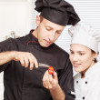 Senior chef teaches young chef to decorate fruit - 图库照片