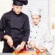Senior chef teaches young chef to properly cut — Stock Photo