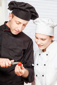 Senior chef teaches young chef to decorate fruit — Stock Photo