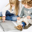 Girl and boy seating near laptop — Stock Photo