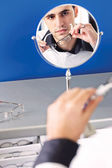 Face of a man in a mirror while he testing eyeglasses — Stock Photo