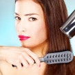 Stock Photo: Womwith long hair holding blow dryer and comb