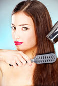 Woman with long hair holding blow dryer and comb — Stock Photo