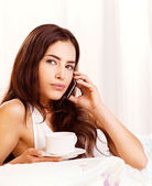 Woman making phone call and holding cup of coffee in bed — Stock Photo
