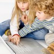 Children turning on computer - Stock Photo