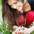 Woman in park gather spring flowers - Stock fotografie