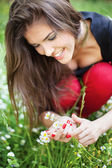 Woman in park gather spring flowers — Stockfoto