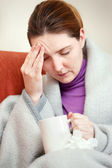 Sick woman covered with blanket at home — Stock Photo