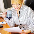 Blond businesswoman checking the papers in office — Stock Photo #8344351