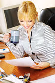 Blond businesswoman checking the papers in office — Stock Photo