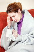Sick woman with a cup of tea in her hand — Stock Photo