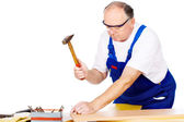 Worker knocking the nail in board — Stock Photo