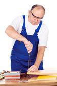 Trabajador de edad media tirando del clavo en tablero — Foto de Stock