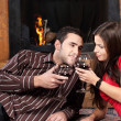 Stock Photo: Couple near fireplace holding glass of wine