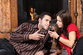 Couple near fireplace holding glass of wine — Stock Photo