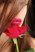 Woman's lips and red rose — Stock Photo