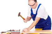 Middle age worker knocking the nail in board — Stock Photo