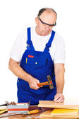 Middle age worker hammering nails in board — Stock Photo