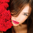 Woman and bouquet of a red carnations — Stock Photo