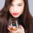Woman with pelt holding glass of brandy — Stock Photo #8952087