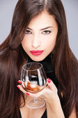 Woman with pelt holding glass of brandy — Stock Photo