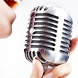 Woman singing on retro microphone — Stock Photo