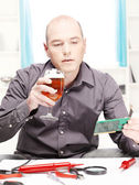 Man with beer doing minor electronic repair at home — Stock Photo
