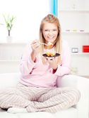 Woman on sofa eating cake at home — Стоковое фото