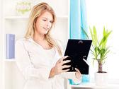 Mujer con marco de foto en casa — Foto de Stock