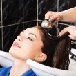 Stock Photo: Hairdresser rinse customers hair
